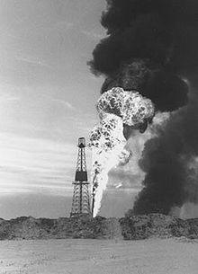 Older Black and white photo of an oil rig with a large flame and plume of smoke behind it.